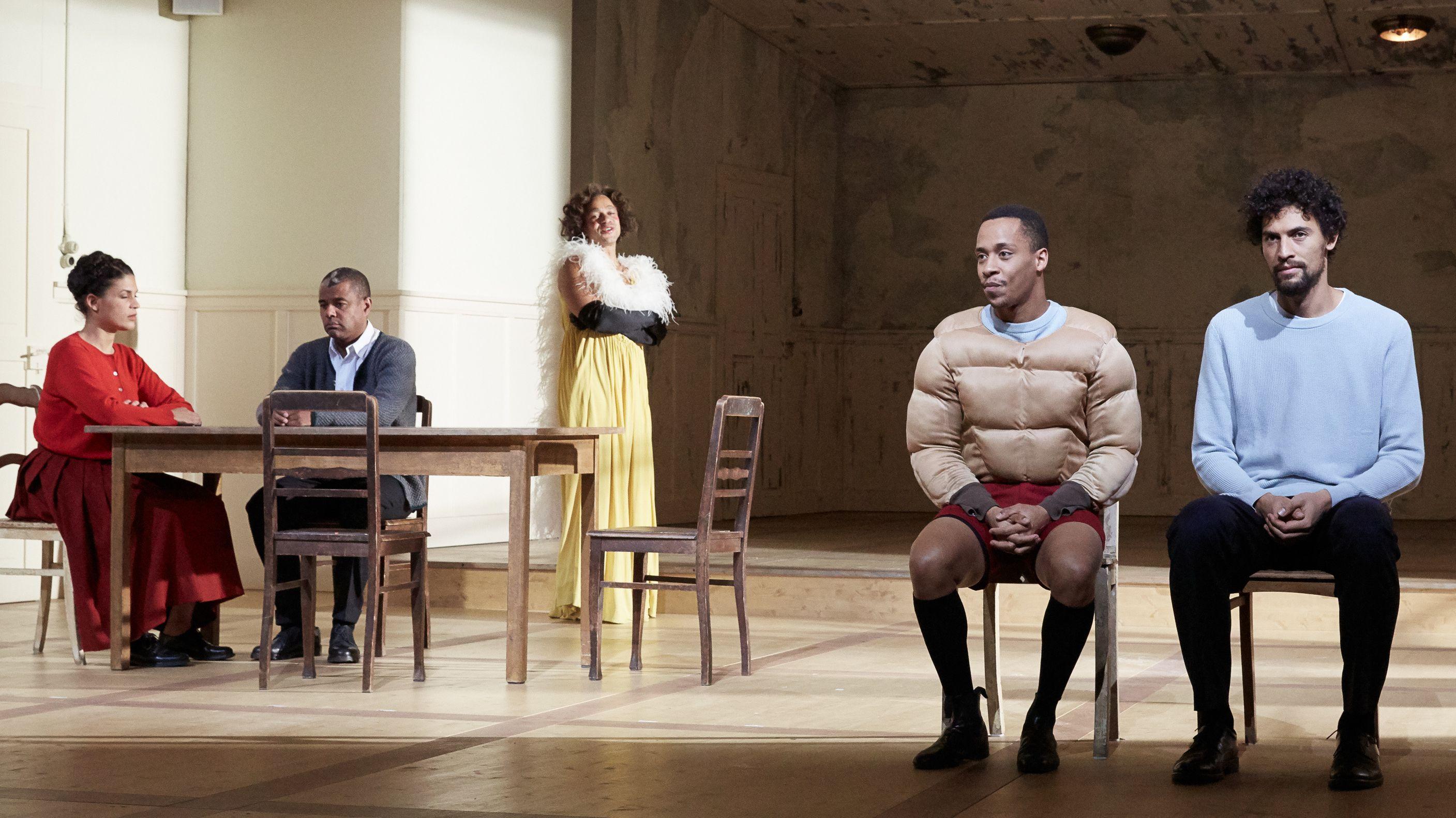 Bühnenszene: Zwei schwarze Schauspieler sitzen auf Stühlen und blicken resigniert ins leere, im Hintergrund sind drei weitere Schauspieler*innen zu sehen