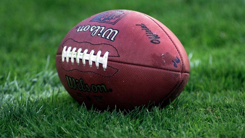 Der eiförmige Ball im American Football liegt auf dem Rasen
