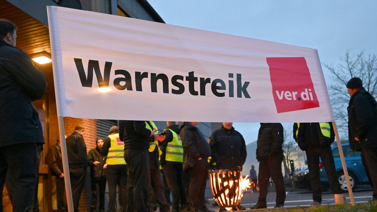 """Symbolbild: Streikende stehen hinter einem Transparent mit der Aufschrift """"Warnstreik"""""""