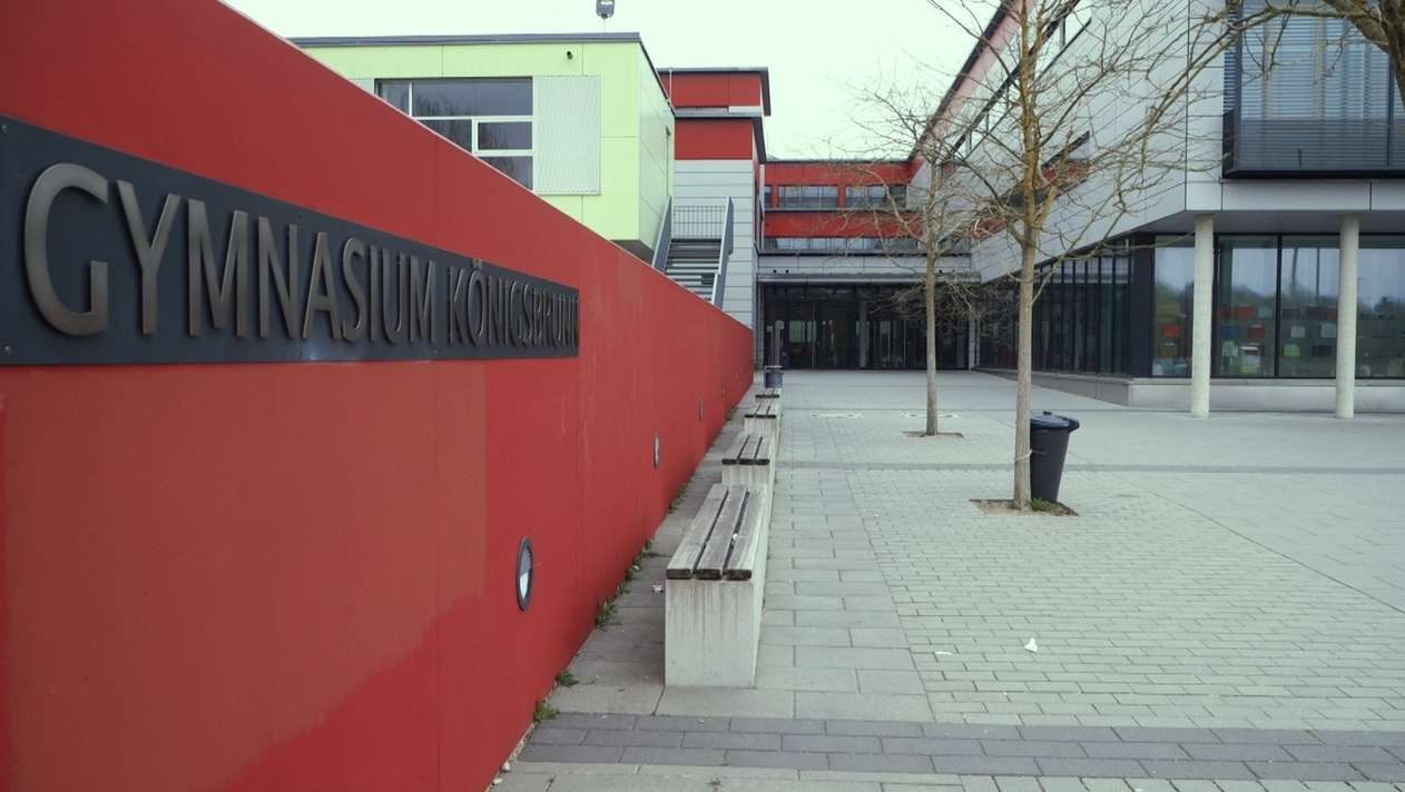 Außenansicht vom Gymnasium Königsbrunn mit Schulhof und roter Mauer