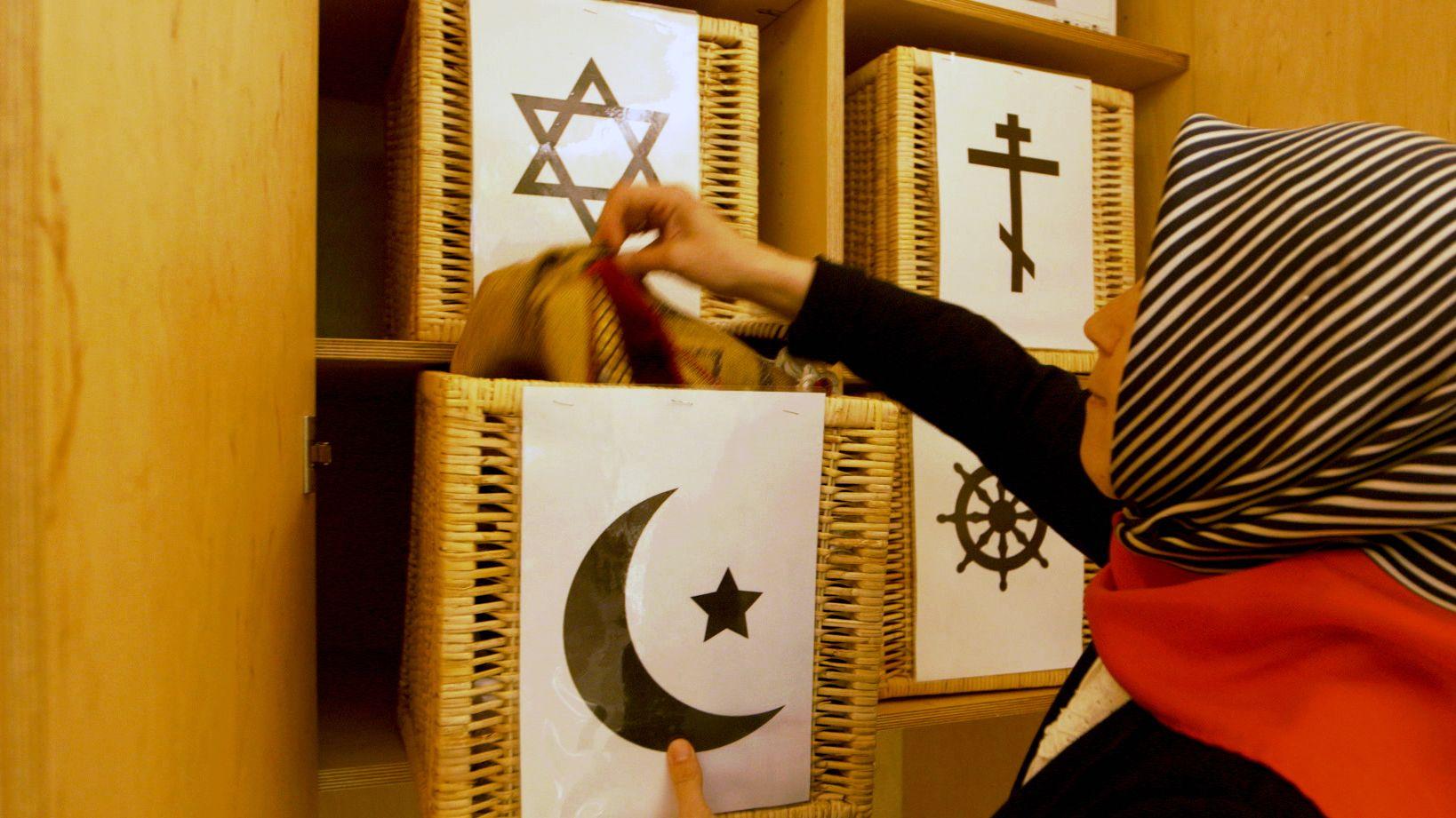 Vier Religionen und vier Körbchen mit passenden Utensilien zum Gestalten des Raumes
