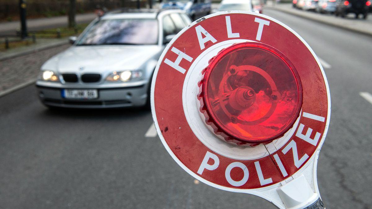 """Polizeikelle mit der Aufschrift """"Halt Polizei"""" vor einem Auto auf einer großen Straße."""