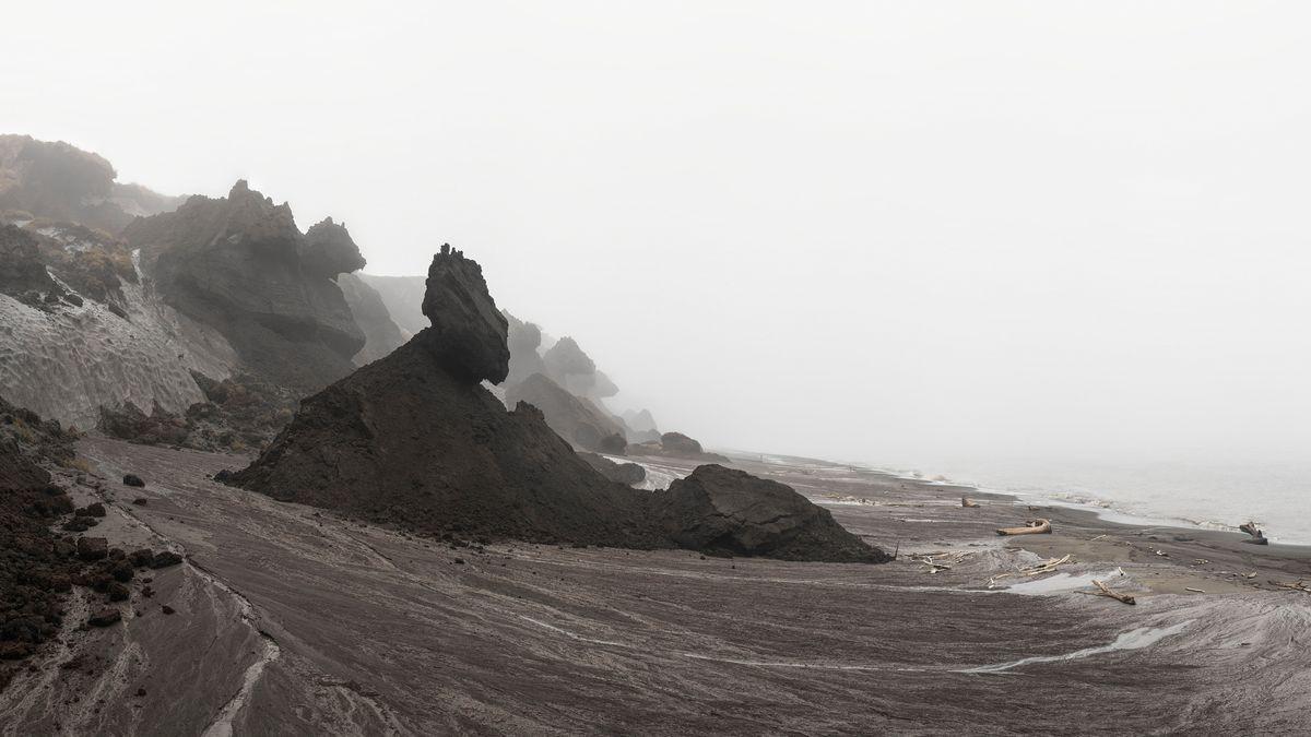 Zerklüftete Klippenlandschaft mit kleinen Booten auf dem Meer auf der Permafrost-Insel Moustakh