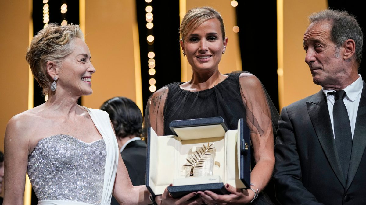 Die Regisseurin Julia Ducournau nimmt in Cannes die Goldene Palme entgegen. Neben ihr: Sharon Stone und Vincent Lindon