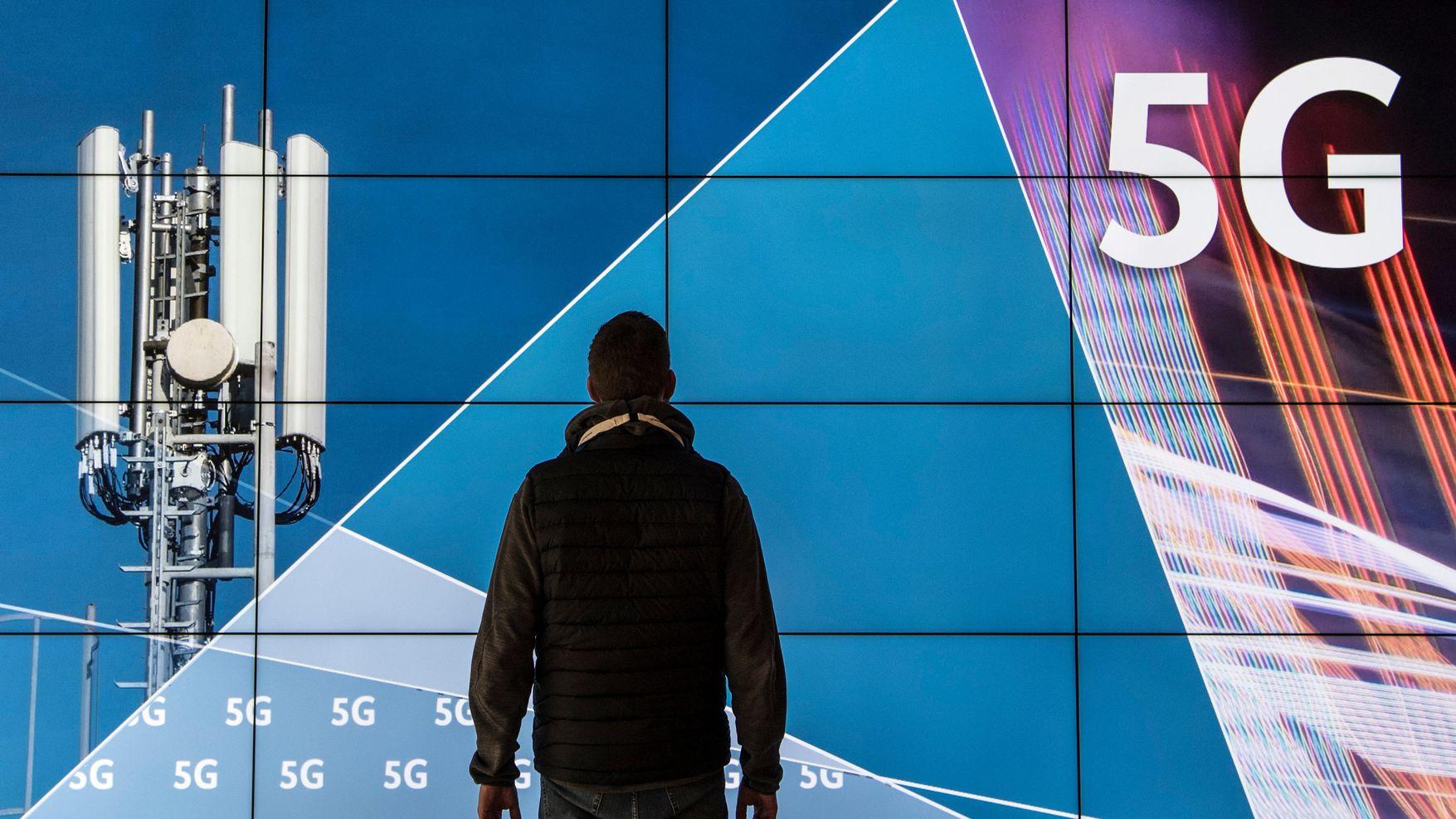 """Ein Mann steht im Gebäude der Bundesnetzagentur vor einer Leinwand mit der Aufschrift """"5G""""."""
