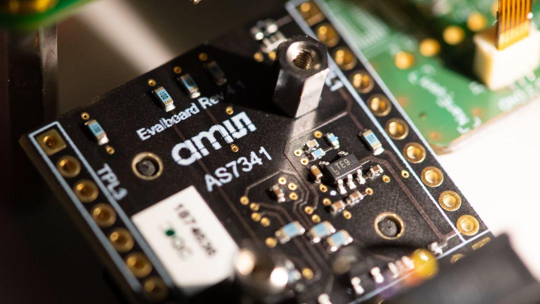Eine Platine mit Sensortechnik von AMS ist während einer Pressekonferenz zu sehen.