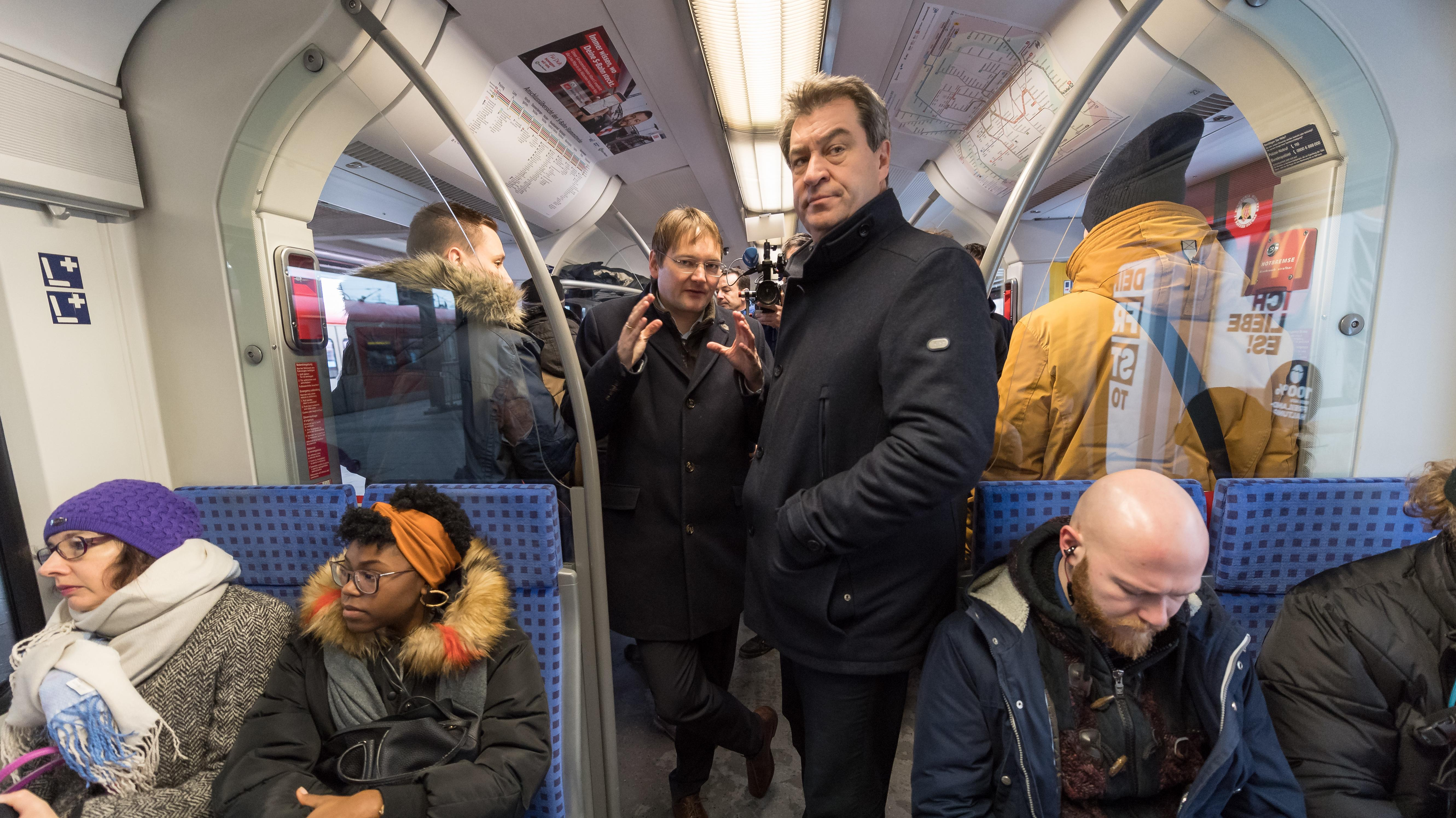 Markus Söder und Hans Reichhart unterhalten sich während einer Fahrt mit der S-Bahn auf der Stammstrecke miteinander.
