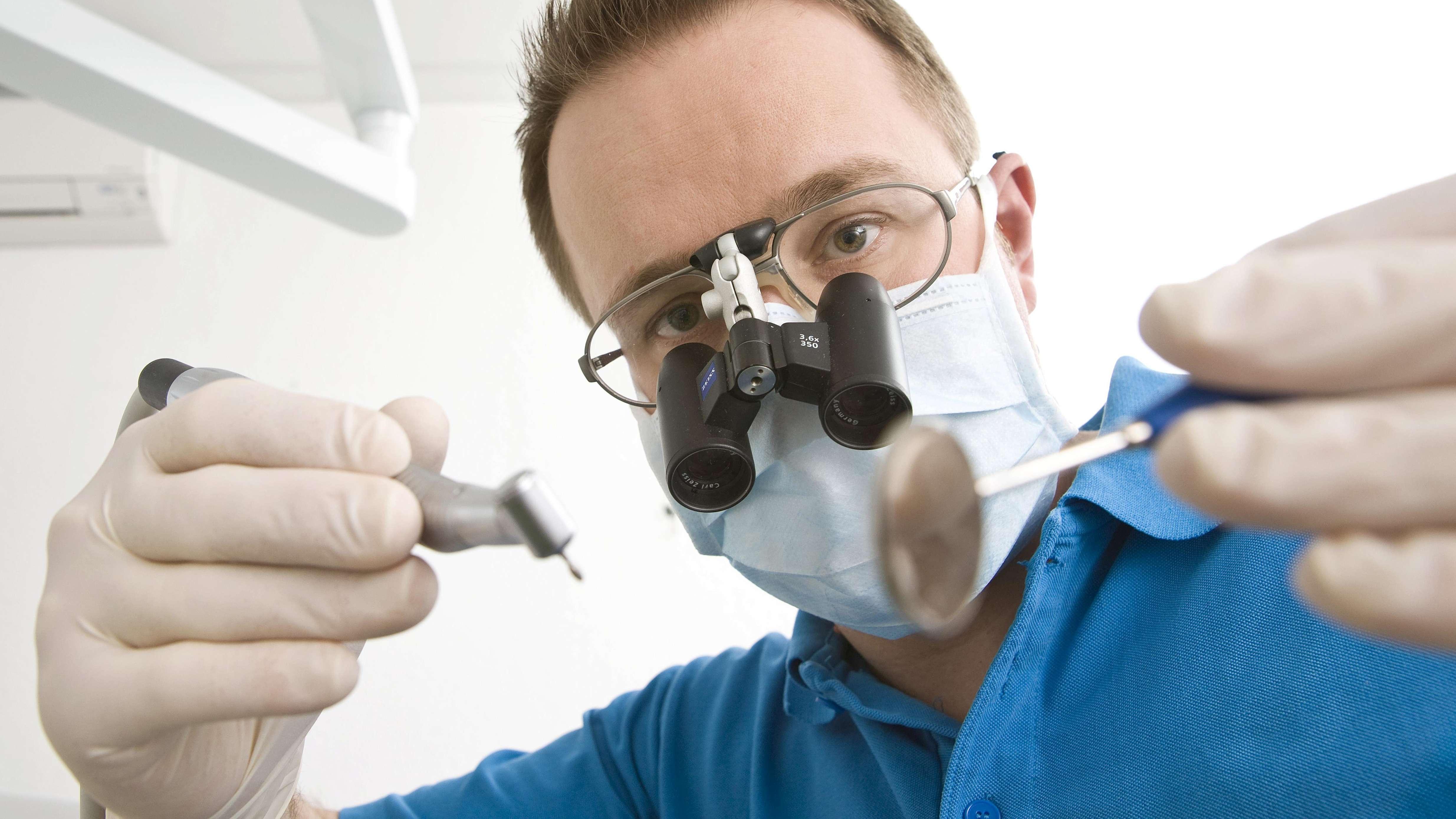 Zahnarzt mit Lupenbrille bei der Behandlung
