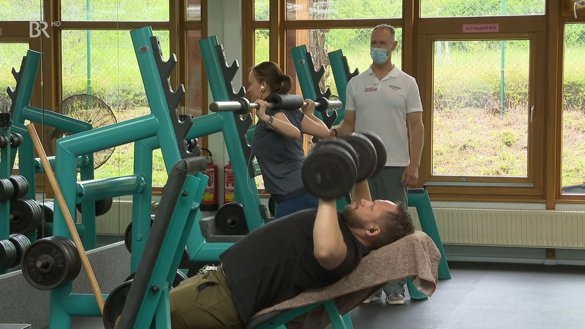 Frau mit Gewichten auf der Schulter macht Kniebeugen. Ein Trainer mit Maske schaut zu.