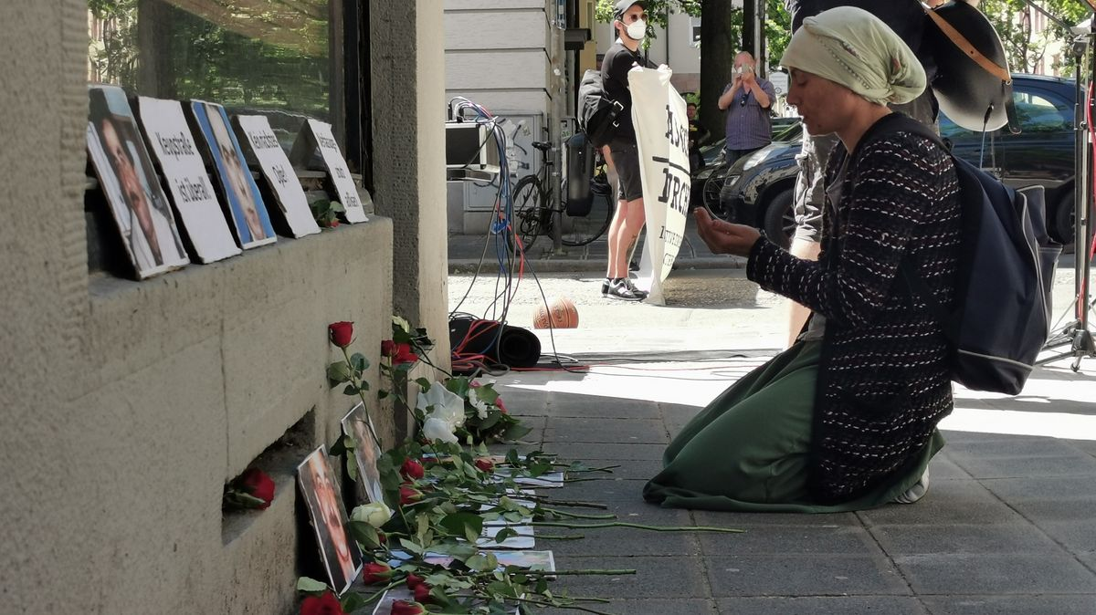 Eine Frau betet vor Fotos und niedergelegten Blumen