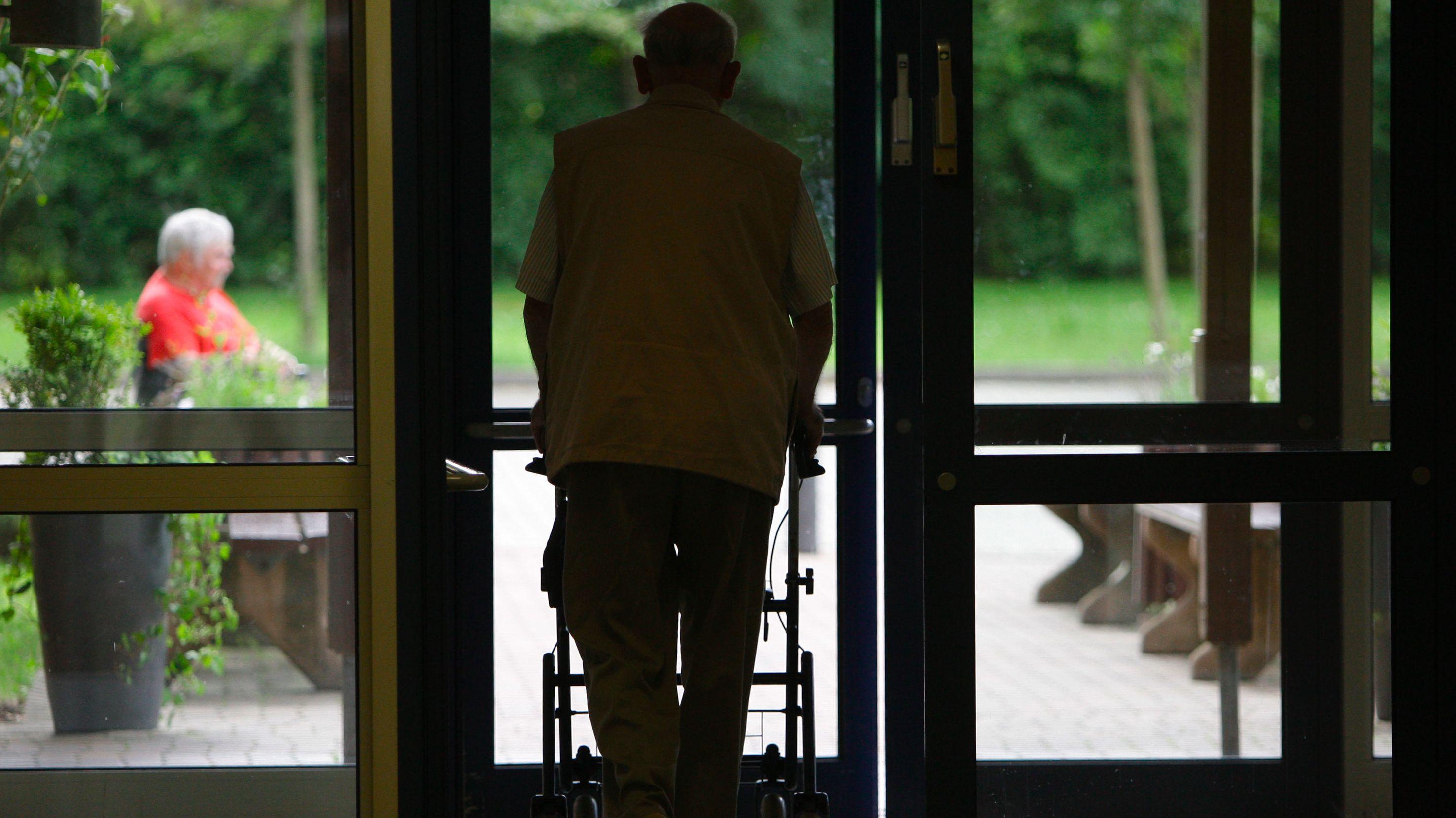 Ein Senior geht mit einer Gehilfe durch eine Tür in einem Altenheim