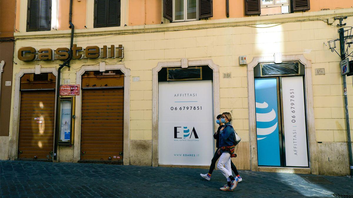 Menschen spazieren an geschlossenen Läden in Italien vorbei.