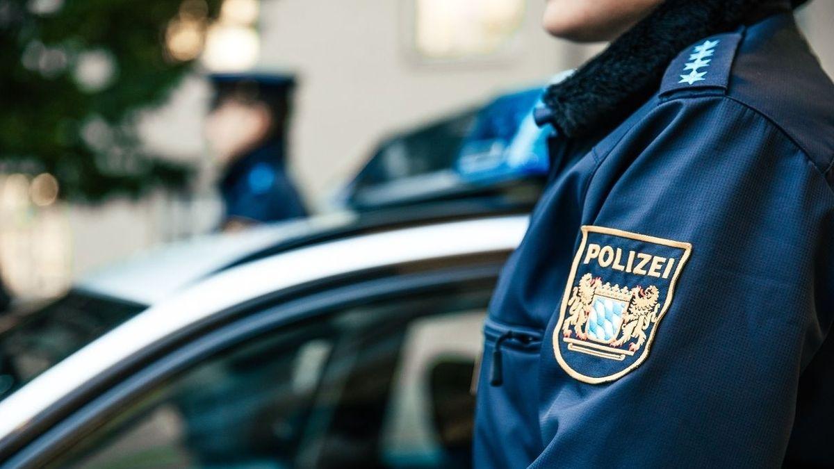 Polizisten in Uniform stehen neben einem Polizeiauto (Symbolbild).