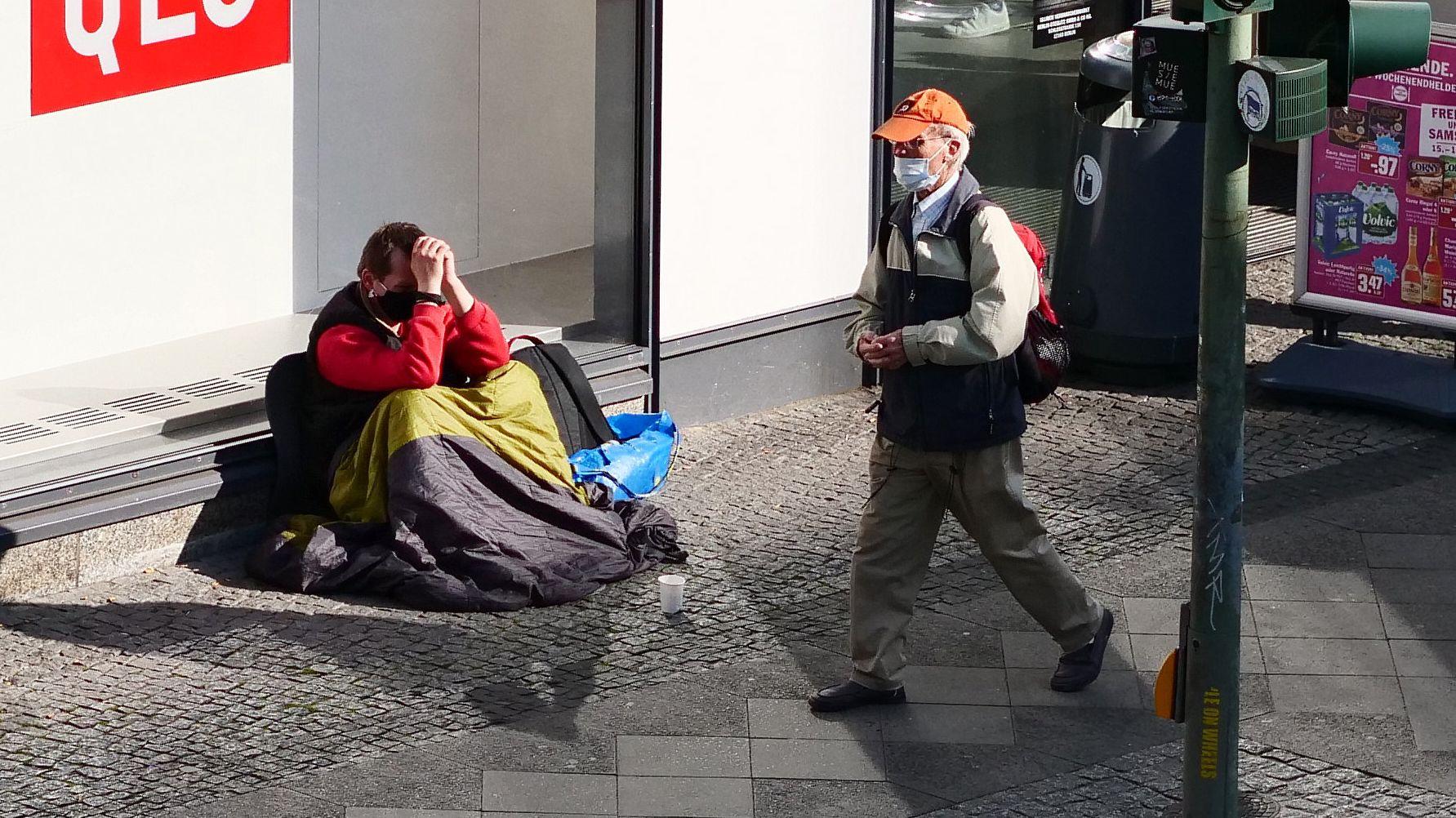 Ein Passant geht an einem Obdachlosen vorbei, beide tragen Mundschutz