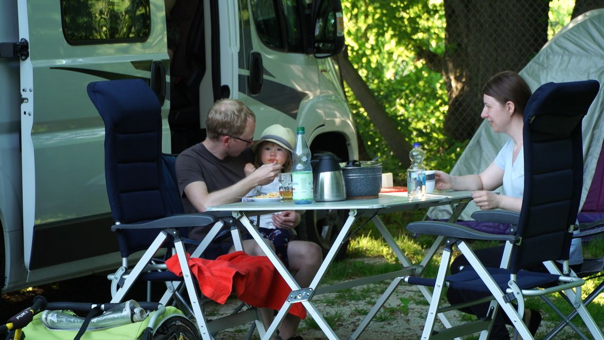 Eine junge Familie sitzt an einem Tisch auf einem Campingplatz.