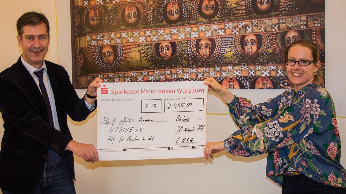"""Oberbürgermeister Christian Schuchardt (CDU) übergibt Spendenscheck an Vera Hoxha von """"Hermine""""."""
