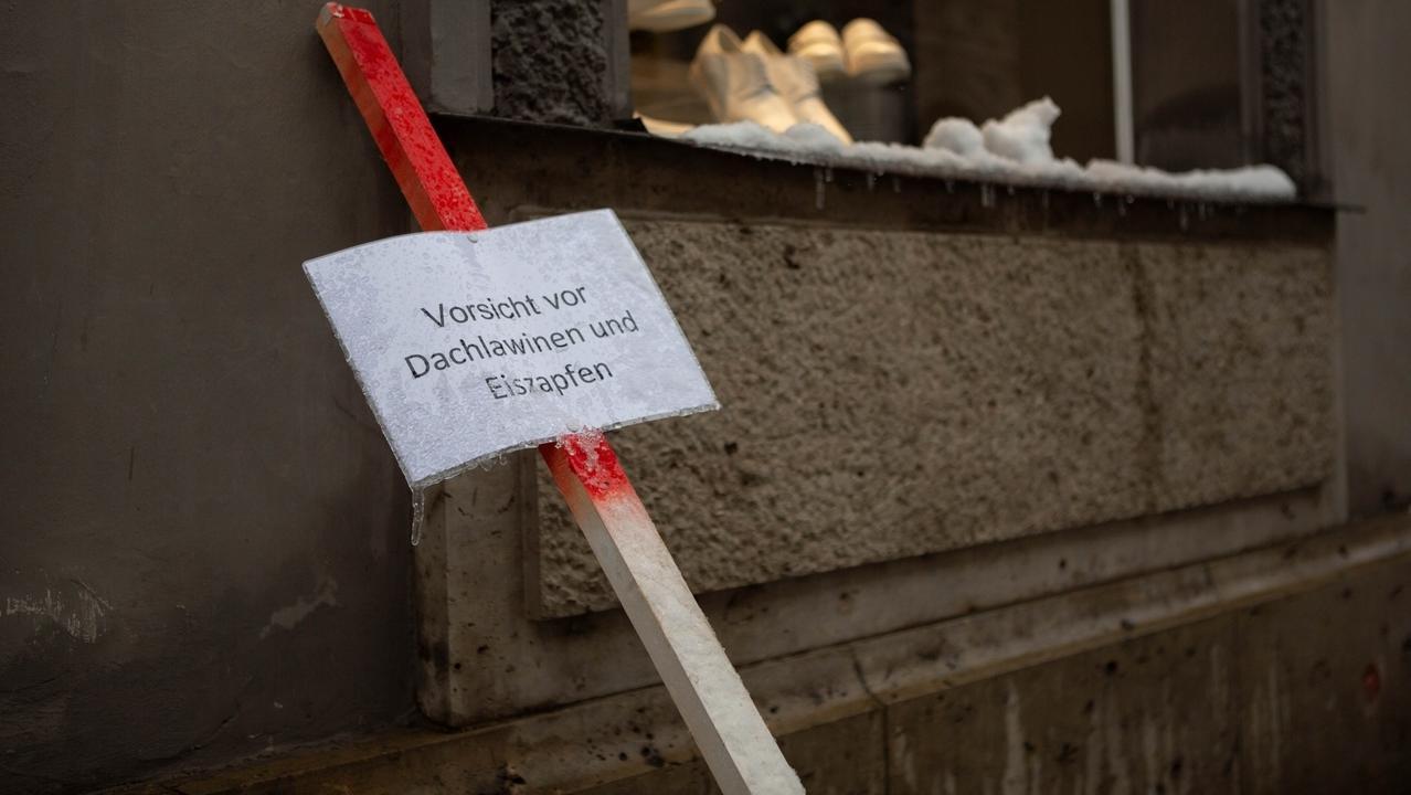"""Schild mit der Aufschrift """"Vorsicht vor Dachlawinen und Eiszapfen""""."""