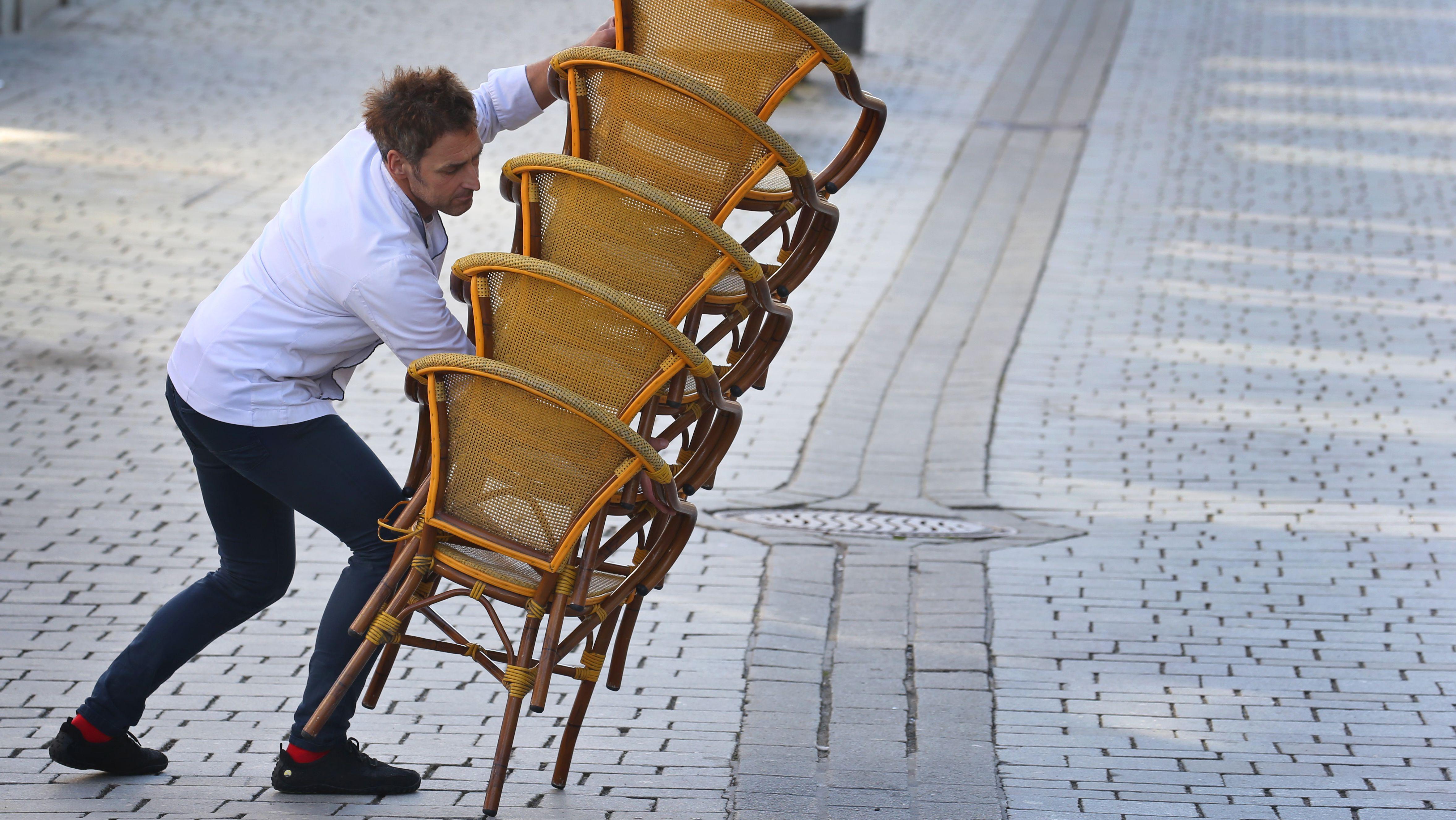 Ein Mitarbeiter eines Straßencafes in Kempten trägt gegen 15 Uhr aufeinander gestapelte Stühle in sein Lokal