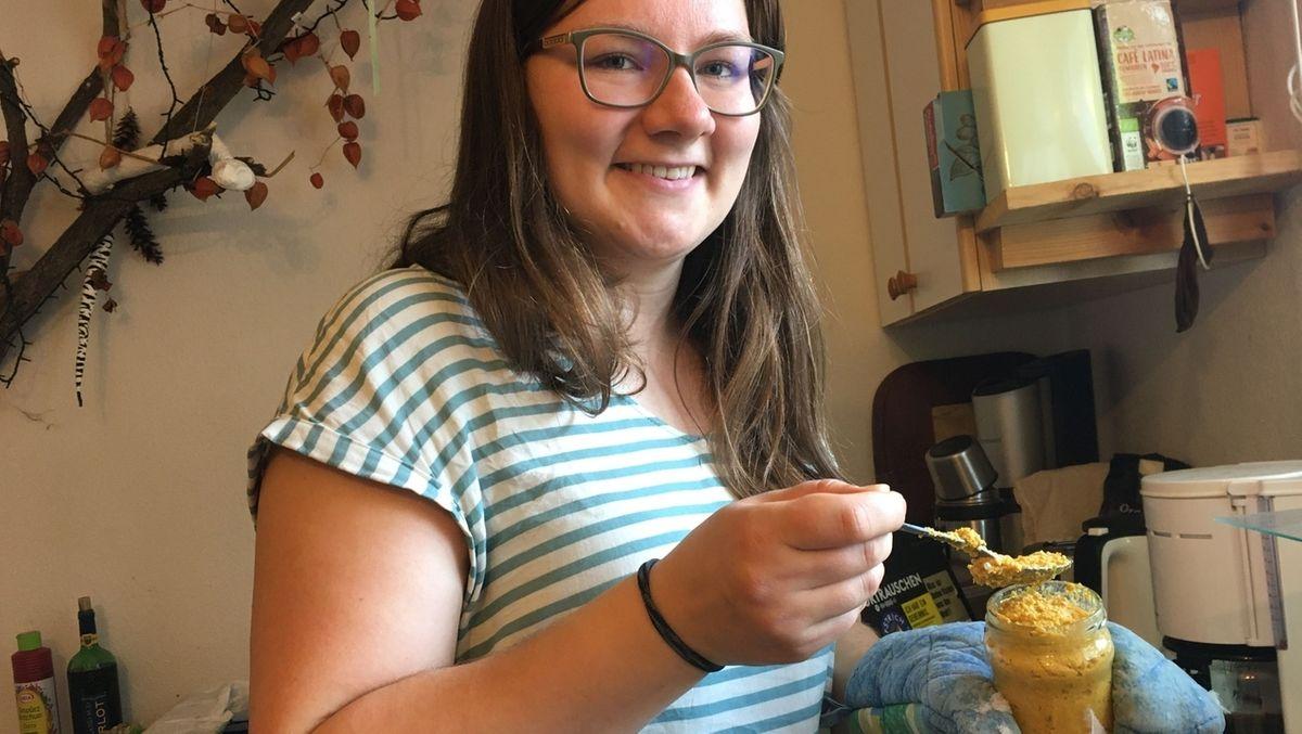 Stefanie Propp steht in einer Küche und hat ein Glas mit ockerfarbenem Mus in der Hand.