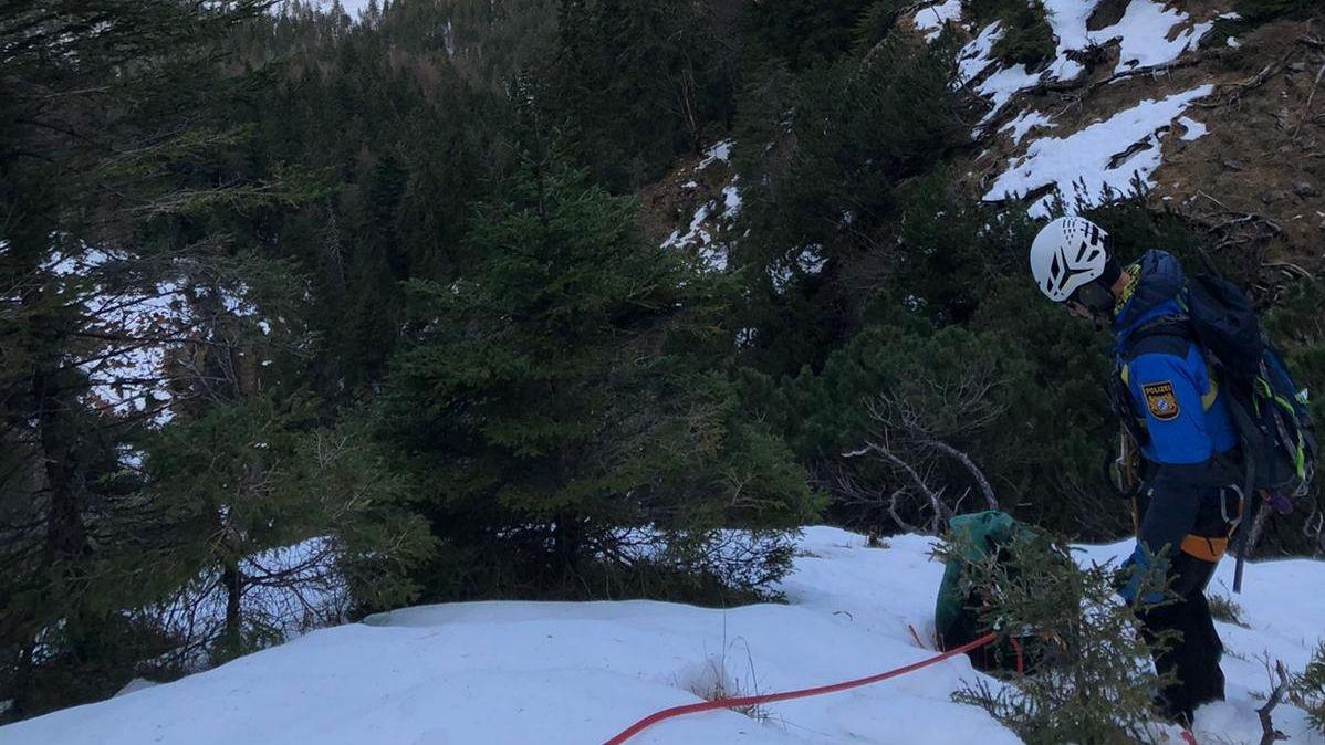 Ein Polizist in Berg- und Kletterausrüstung steht, gesichert mit einem Seil, zwischen Latschenkiefern in einem verschneiten Berghang.