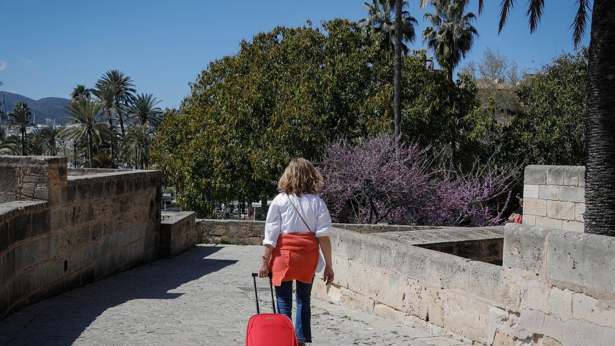 Eine Frau mit Gepäck geht durch eine Straße auf Mallorca.