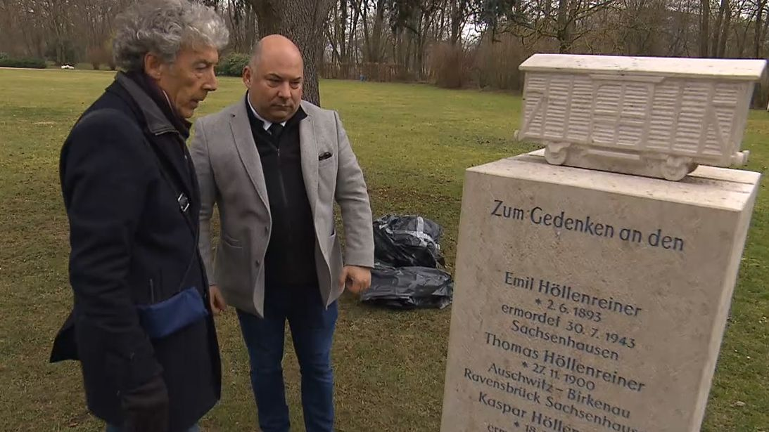 Zwei Männer stehen vor dem Sinti-Gedenkstein.