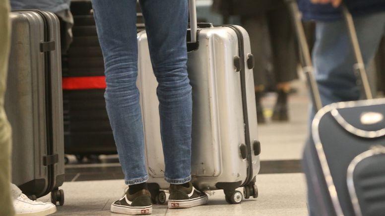 Reisende mit Koffer warten auf ihre Abfertigung | Bild:dpa-Bildfunk/David Young
