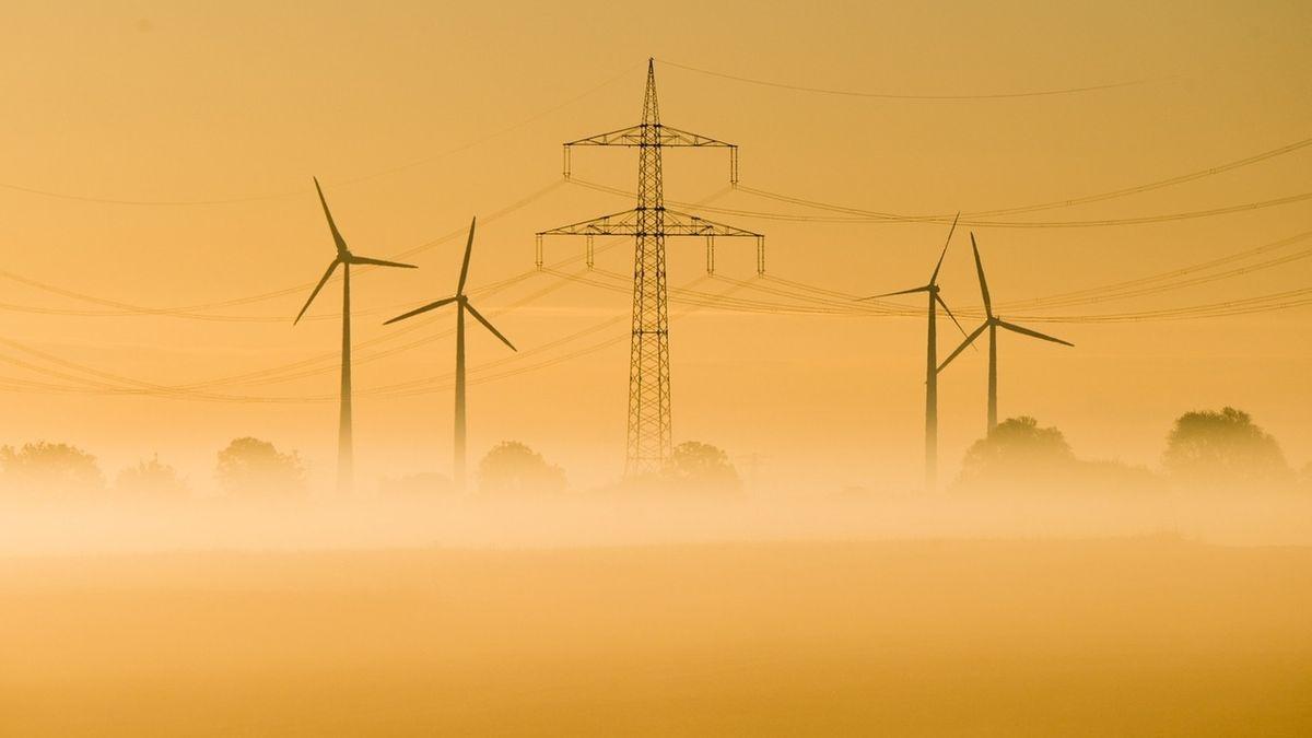 Stromleitung und Windräder im Morgennebel