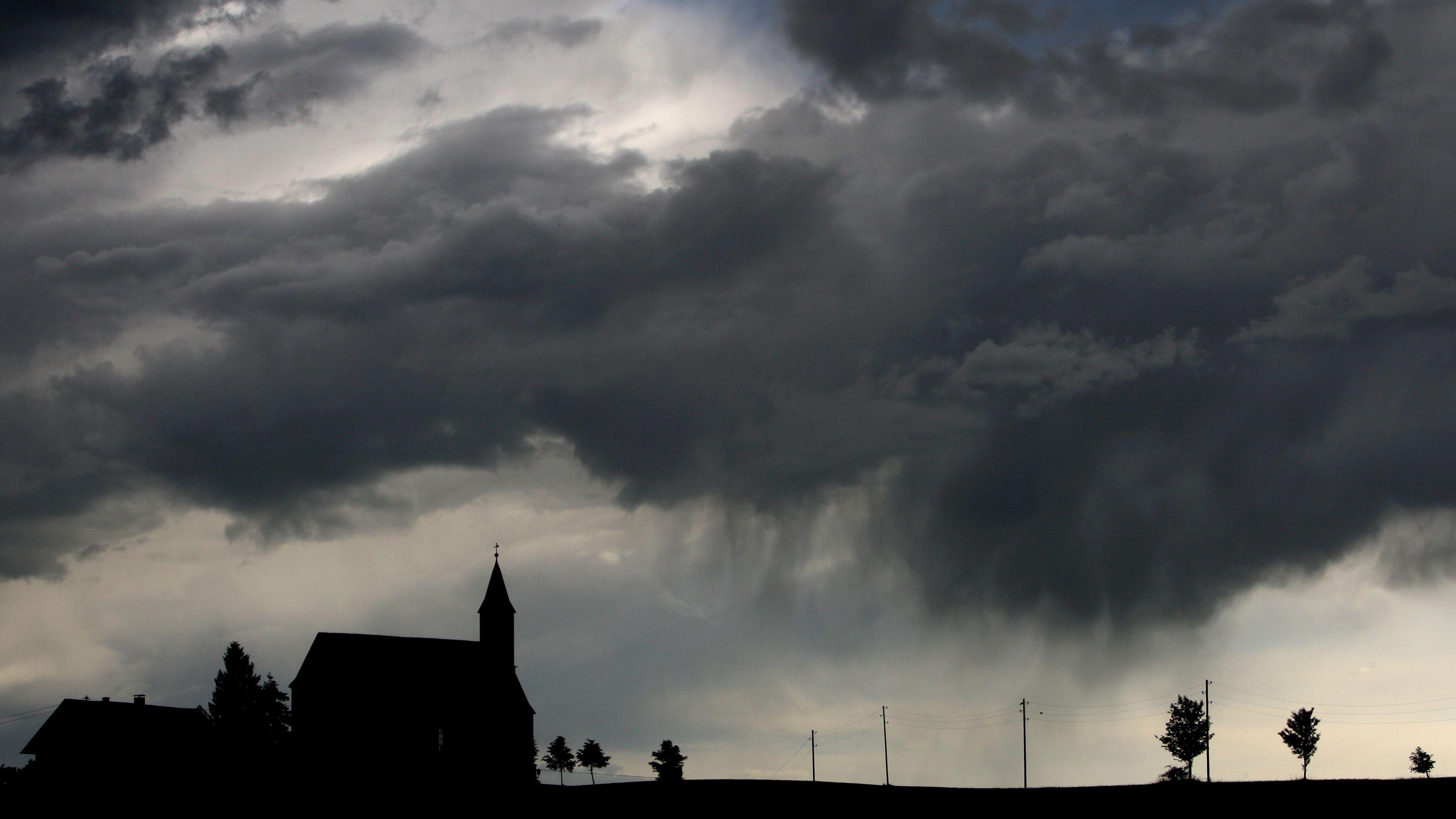 Gewitterwolken regnen sich am Sonntag (05.06.2011) über der Kapelle Sankt Alban bei Görwangs (Schwaben) ab.  (Archivbild)