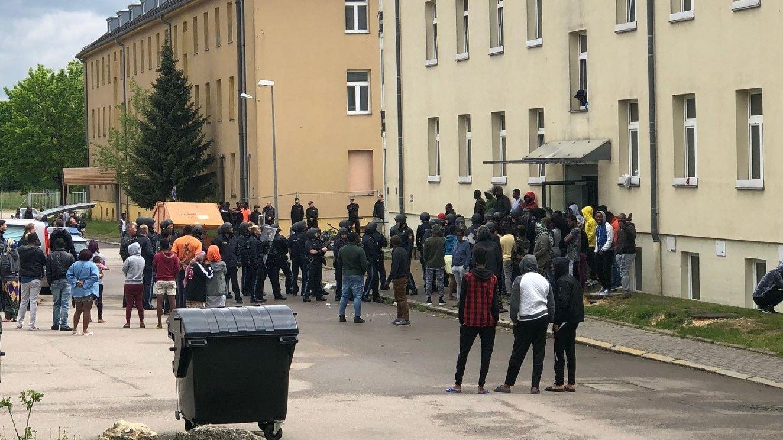 Polizisten und Bewohner vor dem Ankerzentrum