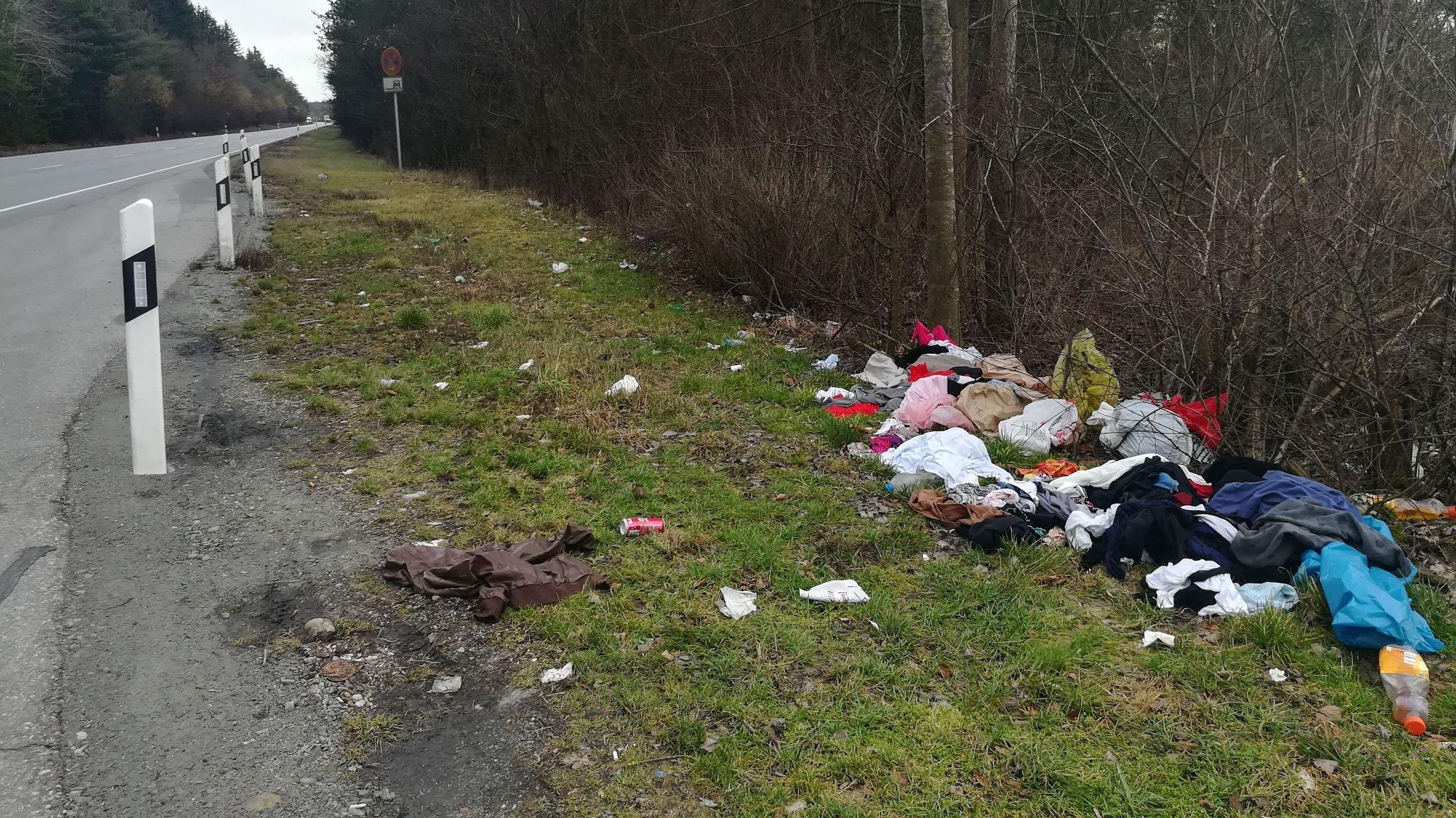 Das Bild zeigt illegal am Straßenrand entsorgte Altkleider in Mülltüten.