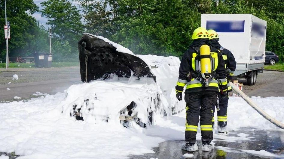 Die Feuerwehr löscht das brennende Auto mit Schaum