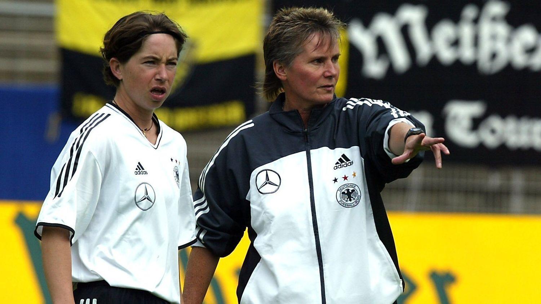 Fußball-Bundestrainerin Tina Theune (rechts) unterhält sich bei einem Spiel im Jahr 2003 mit einer Spielerin.