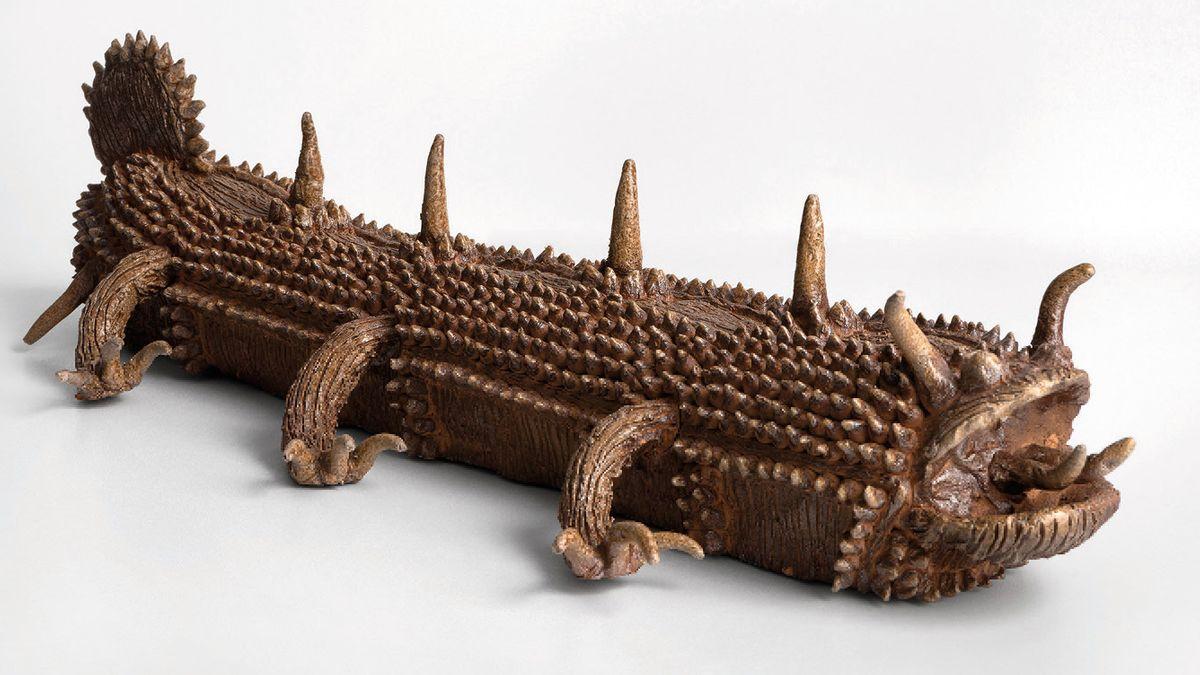 Keramik-Skulptur eines reptilienartigen Schuppenwesens mit Hörnern und aufgerissenem Maul in Braun