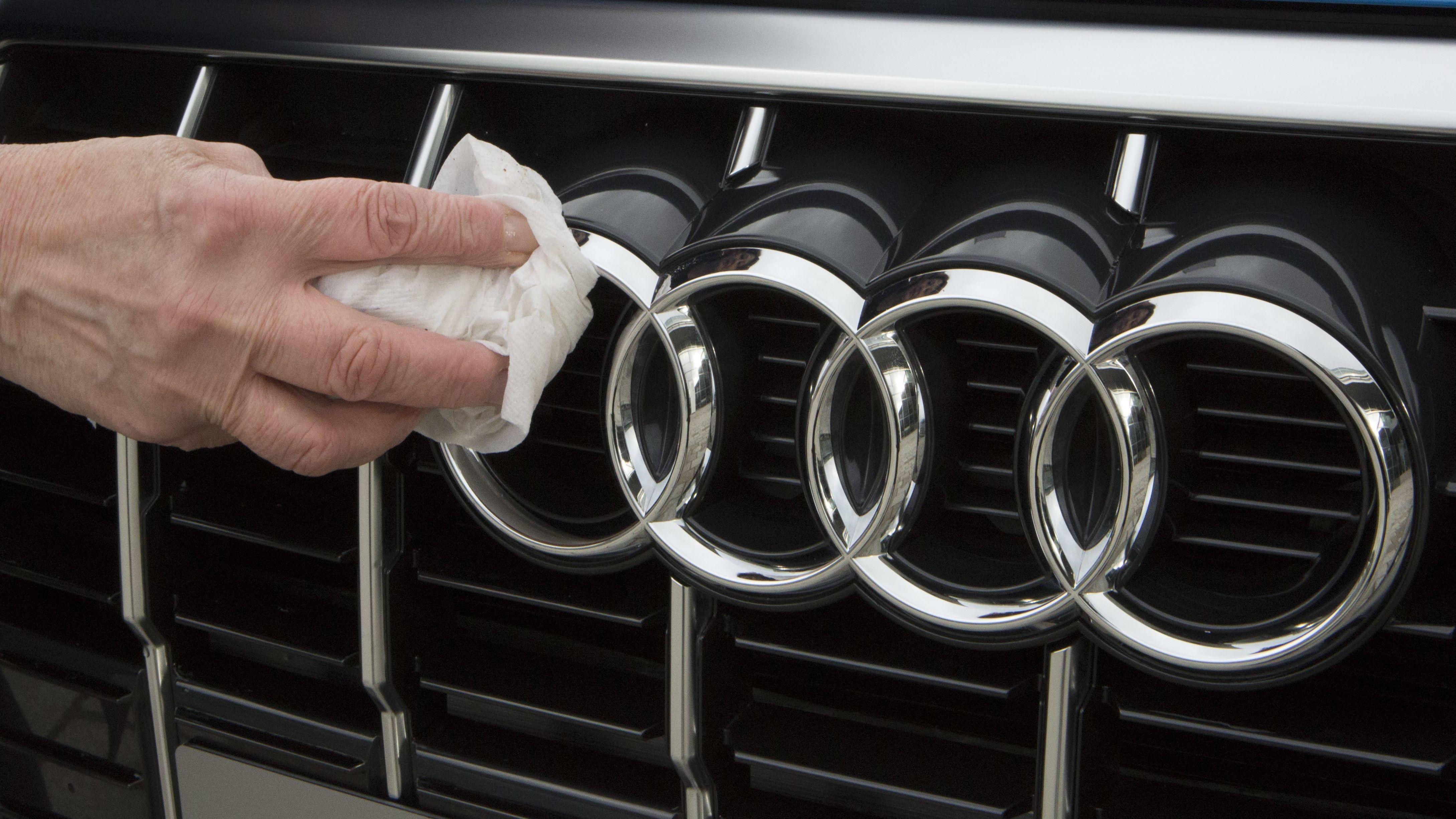 Ein Mitarbeiter poliert einen Audi-Schriftzug.
