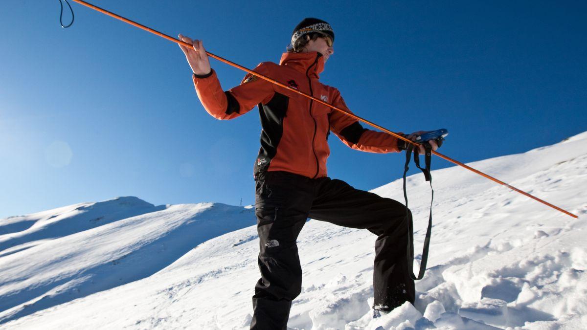 Mann stochert mit Lawinensonde im Schnee auf der Suche nach Verschütteten.