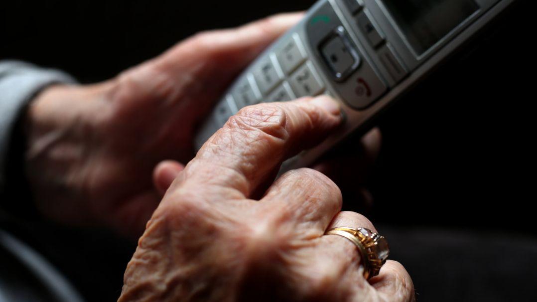 Eine ältere Frau tippt auf einem schnurlosen Festnetztelefon. (Symbolbild)