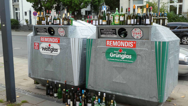 Ein voller Glascontainer für Altglasrecycling mit vielen leeren Flaschen auf und neben dem Sammelcontainer