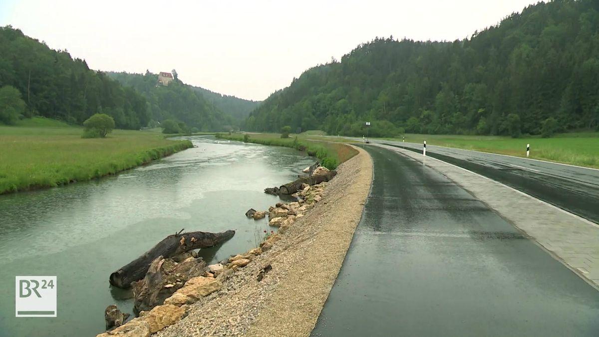 Parallel zur Wiesent zieht sich neben der Straße der asphaltierte Radweg durch das Wiesenttal, im Hintergrund Wälder.