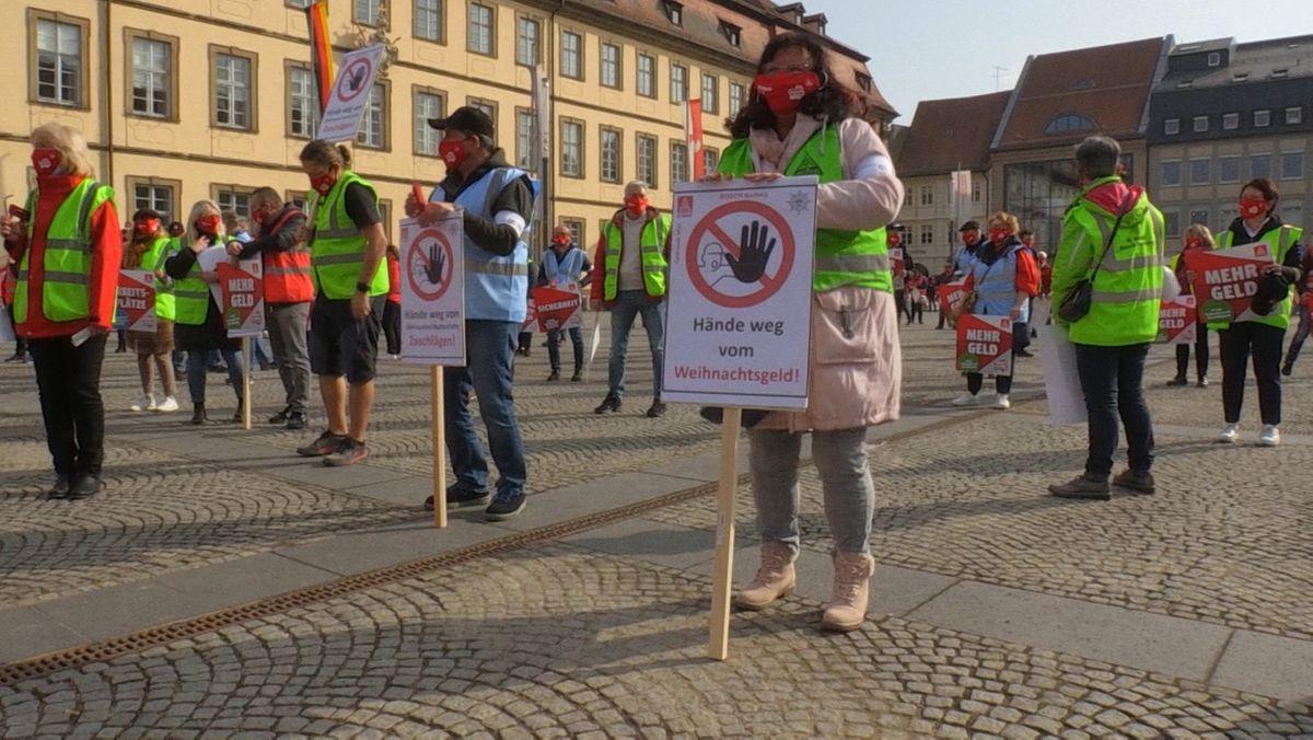 """Streikende Frauen und Männer halten Transparente in Händen, auf denen unter andrem """"Mehr Geld"""" zu lesen ist."""