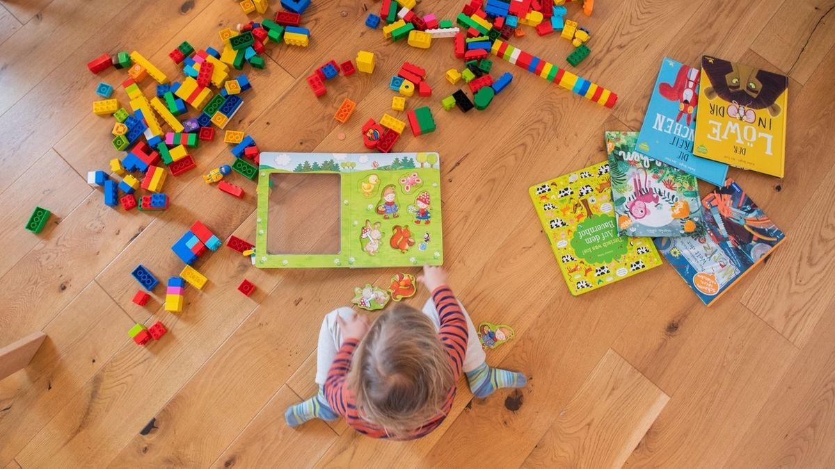 Kind spielt mit Spielsachen auf dem Boden