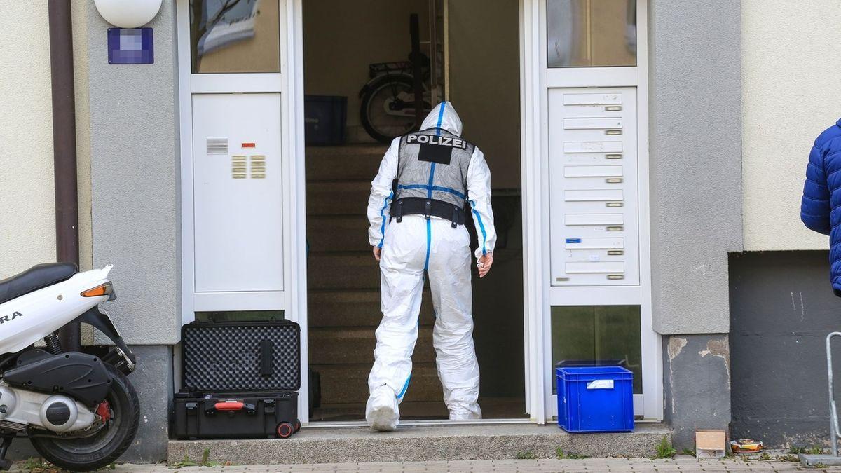 """Ein Mann in einem weißen Schutzanzug, auf dessen Rücken """"Polizei"""" zu lesen ist, geht in ein Wohnhaus."""