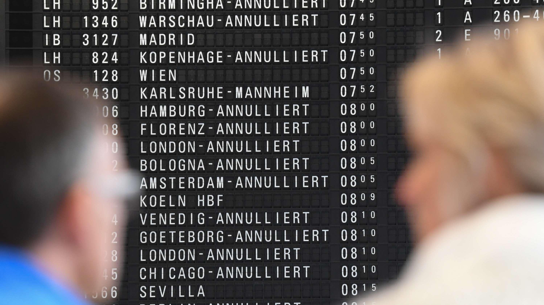 Ein Mann und eine Frau schauen auf eine Flughafenanzeige mit annullierten Flügen