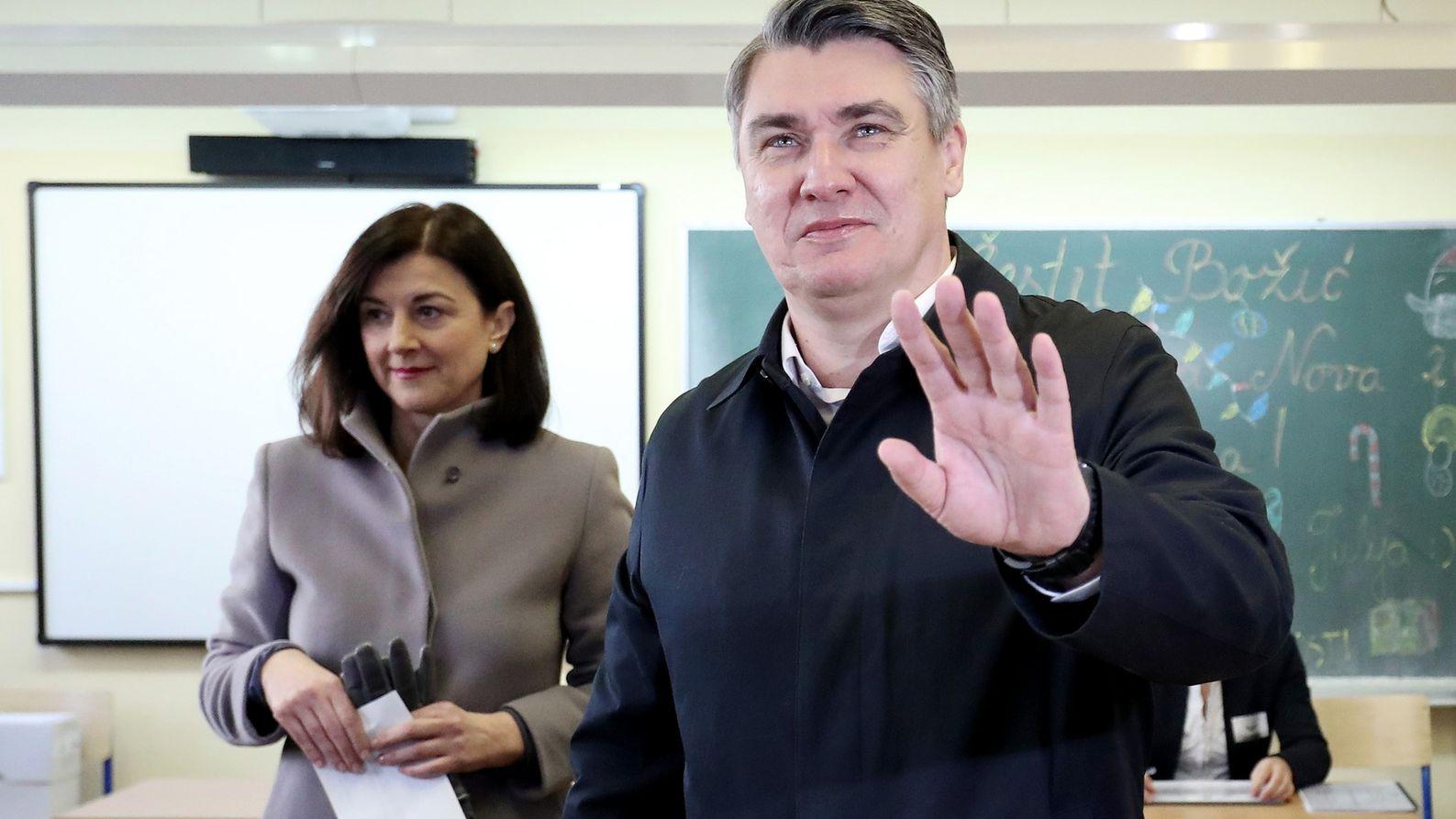 Zoran Milanovic wirft in Begleitung seiner Frau seinen Stimmzettel für die Stichwahl in eine Wahlurne.