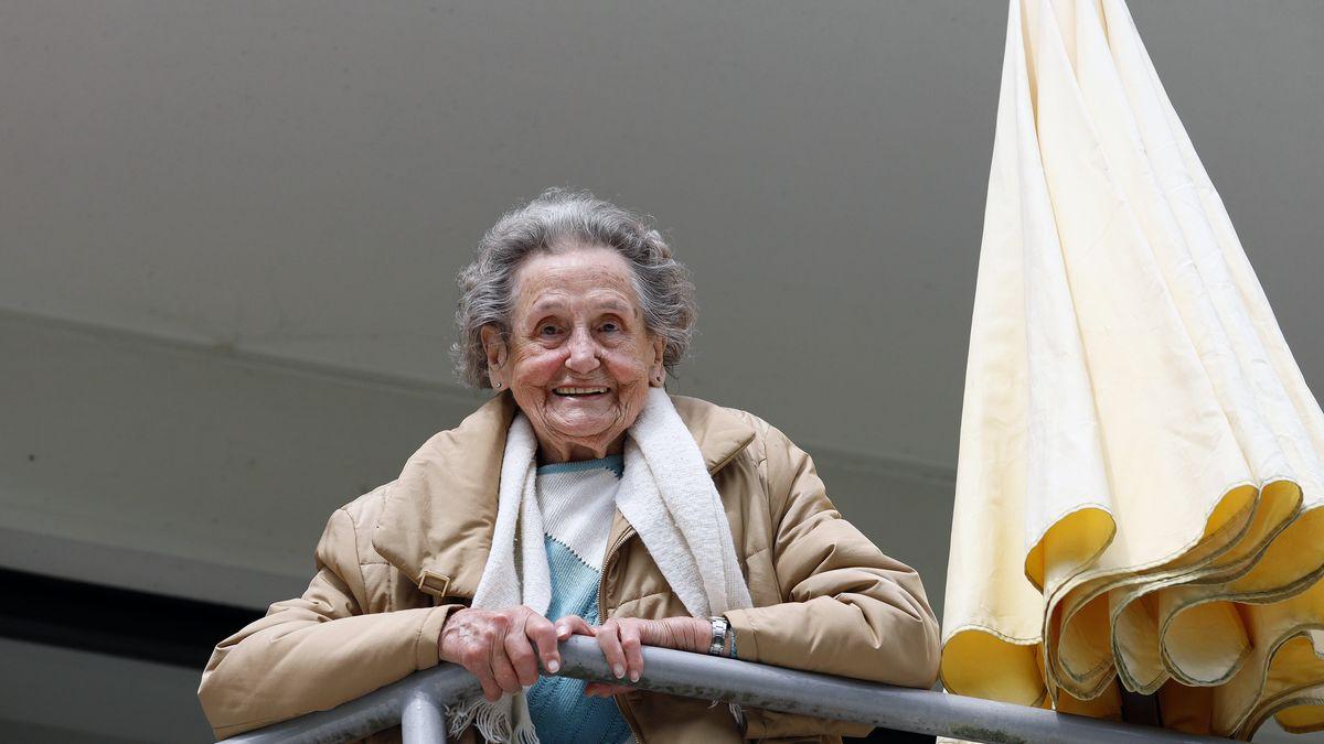 Seniorin lehnt über einem Balkon und schaut nach unten.