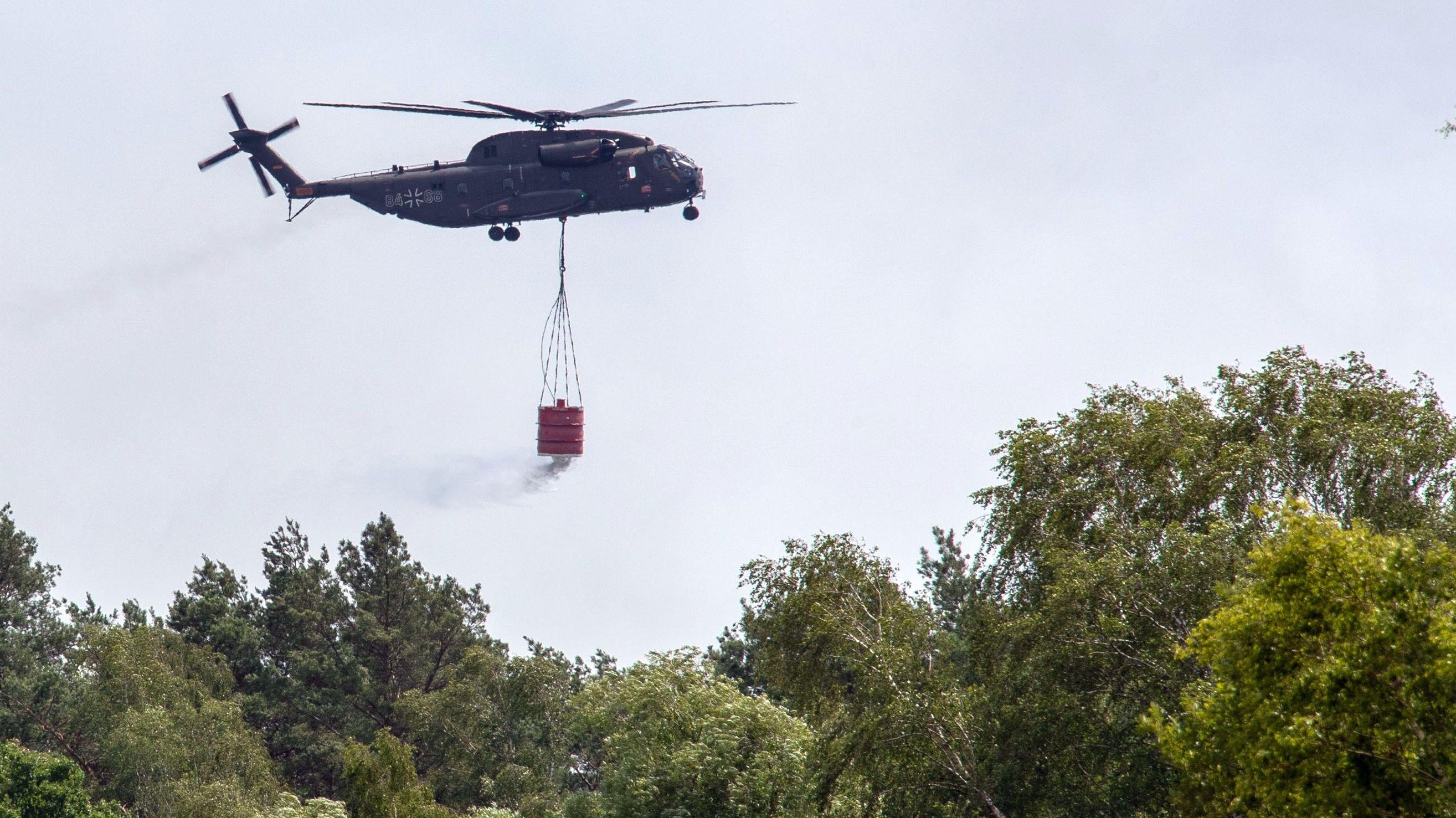 Ein Hubschrauber der Bundeswehr wirft in der Nähe der evakuierten Ortschaft Jessenitz-Werk Löschmittel ab