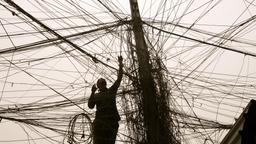 Elektriker im Irak bei der Arbeit in einem Gewirr aus Stromleitungen   Bild:dpa-Bildfunk / Ali Abbas