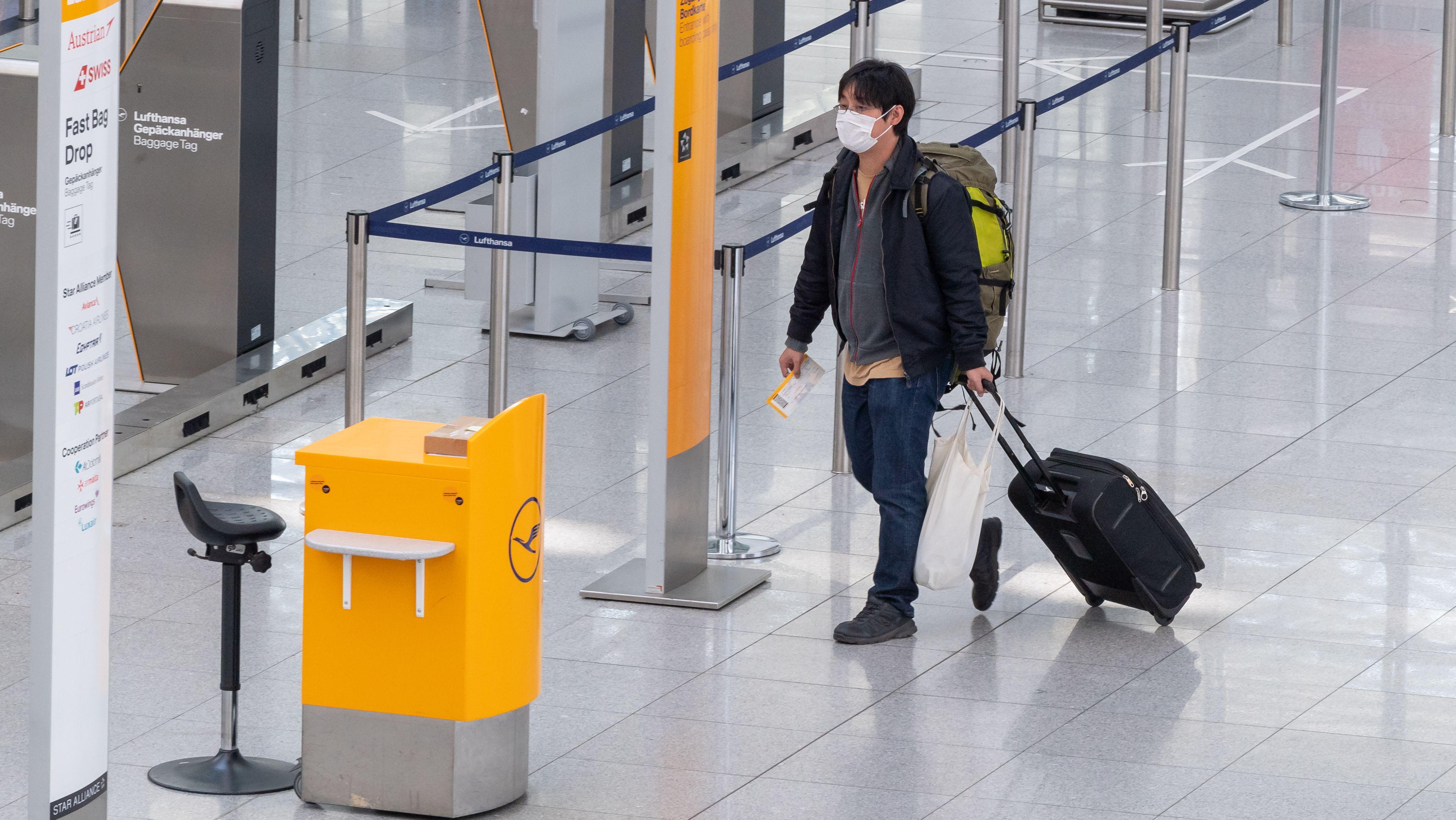 Ein Fluggast mit Mundschutz geht am 18.03.2020 zum Check-in Schalter der Lufthansa am Flughafen München.