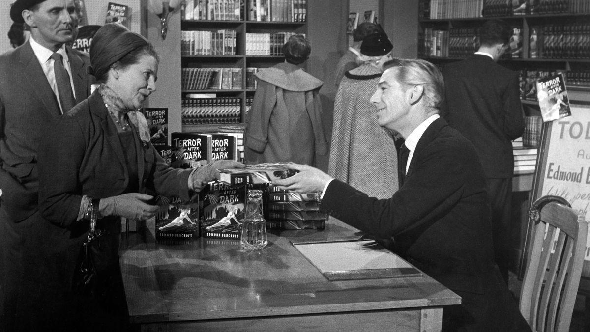 """Ein Autor überreicht nach einer Lesung einer Frau sein Buch - Ausschnitt aus dem Film """"Das schwarze Museum"""""""