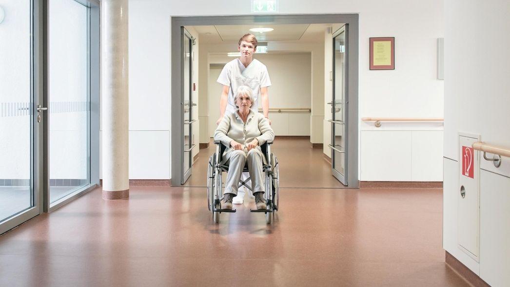 Krankenpfleger schiebt ältere Patientin im Rollstuhl.